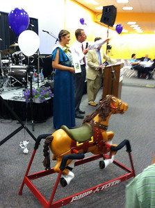 Auctioneer Dave Madsen, assisted by one of the Holyoke Colleens, auctioned off donated item such as this hobby horse.