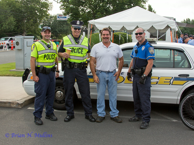 The legendary Dominick Moschini, Plainville's Superintendent of Roadways, poses with (L-R) Ofc. Mark Connoy, Cpl. Patrick Buden, and Ofc. Stephen Chase.