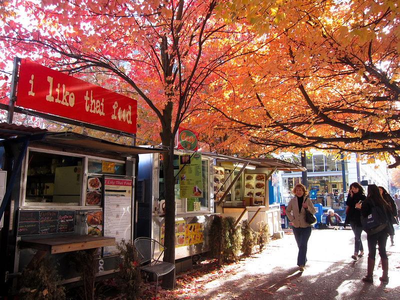Food trucks under autumn foliage