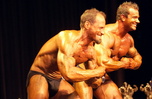 Record-Eagle/Garret Leiva<br /> Chad Krusniak, right, and Dave Fehrenbach pump up their muscles for the judges in the Tall Men class at the 29th annual Grand Traverse Bodybuilding and Figure Championship presented by Fit For You Health Club Saturday at the Leelanau Sands Showroom.