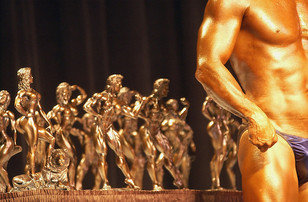 Record-Eagle/Garret Leiva<br /> A competitor in the Tall Men class stands next to the array of trophies up for grabs at the 29th annual Grand Traverse Bodybuilding and Figure Championship presented by Fit For You Health Club Saturday at the Leelanau Sands Showroom.