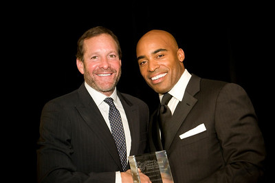 Steve Guttenberg accepts his award from football great Tiki Barber