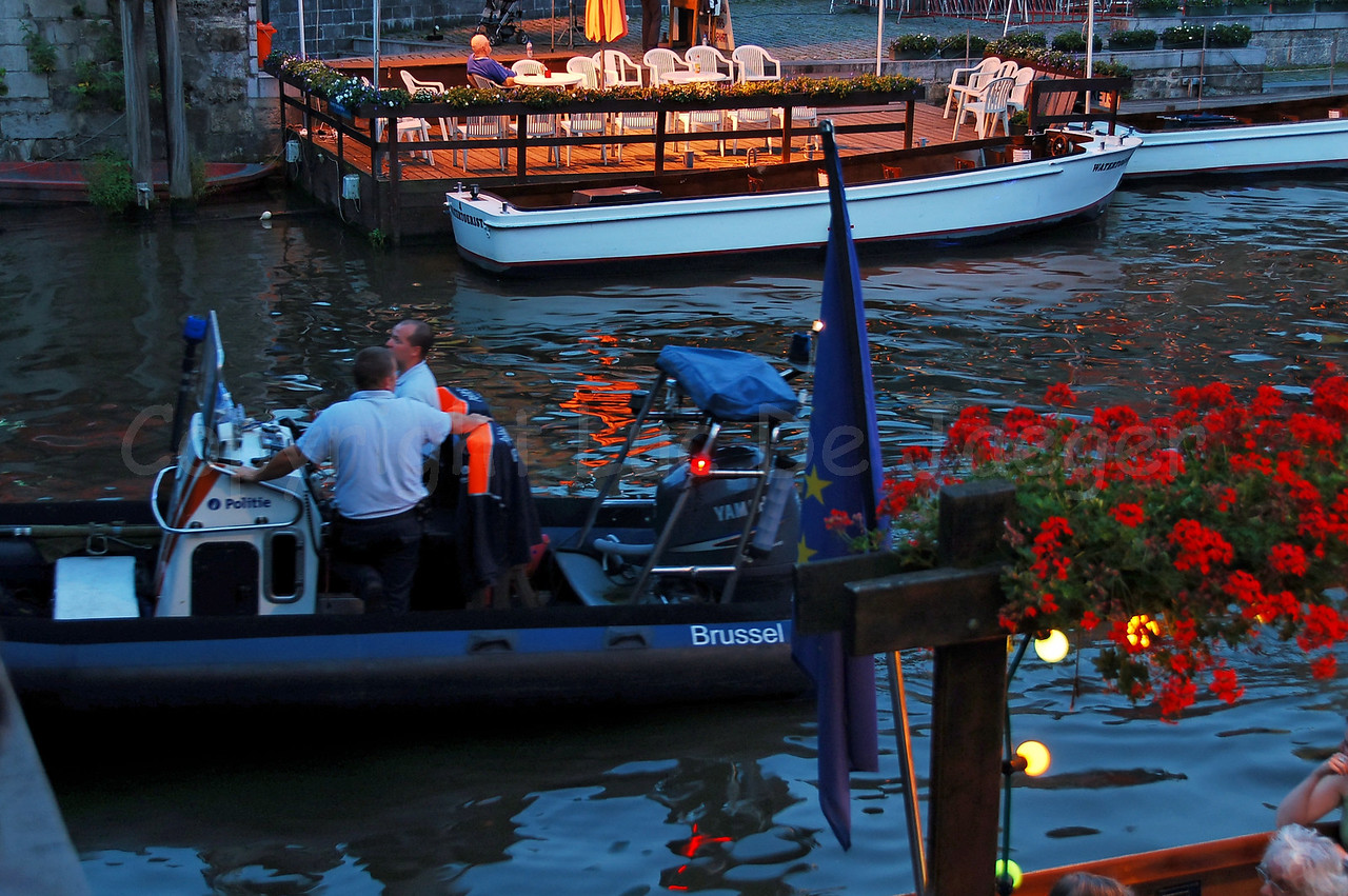 A police boat of the federal police on patrol at the highly colorful Pole Pole Festival during the Ghent Festivities (Gentse Feesten). This festival is one of the many attractions bringing thousands of people to the place between Graslei and Korenlei.