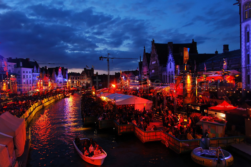 The highly colorful Polé Polé Festival during the Ghent Festivities (Gentse Feesten) 2009 in Ghent (Gent), Belgium is one of the many attractions bringing thousands of people to the place between Graslei and Korenlei. Photo of the Festival captured from the St Michielsbrug (St Michael's bridge) at night under very cloudy weather. This is NO HDR image!