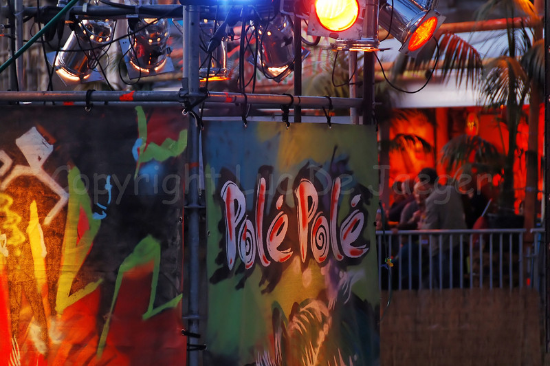 The highly colorful Polé Polé Festival during the Ghent Festivities (Gentse Feesten) 2009 in Ghent (Gent), Belgium is one of the many attractions bringing thousands of people to the place between Graslei and Korenlei. Photo of the lighting captured at sunset.