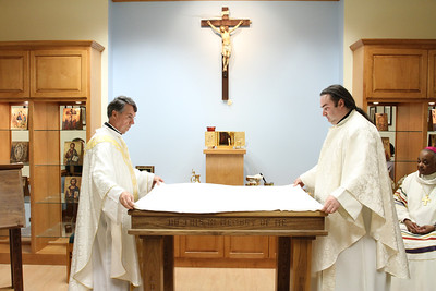 Georgia State University chaplain Father Stephen Lyness, right, and Father David Dye, the administrator of Mary Our Queen Church, Norcross, prepare the altar for the Liturgy of the Eucharist.