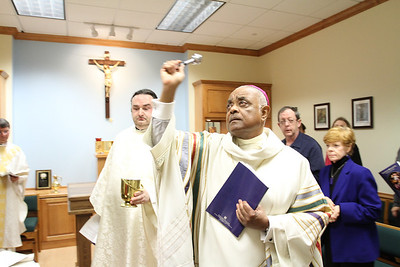 Assisted by Father Stephen Lyness, Georgia State University chaplain, Archbishop Wilton D. Gregory leads the sprinkling rite around the chapel.