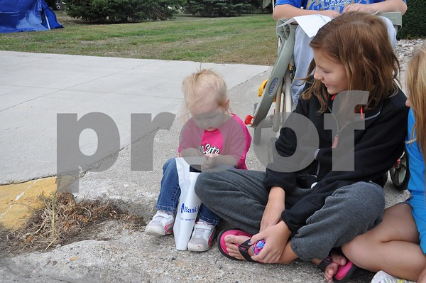Riley Phillips deals with her candy bag while big sister Katelyn Phillips watches.