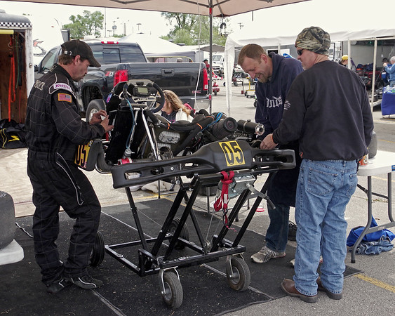 Kart racer Earl Smock of Speedway prepares his ride for competition with the help of friends Ronnie Compton and Ted Knight, both of Shelbyville.