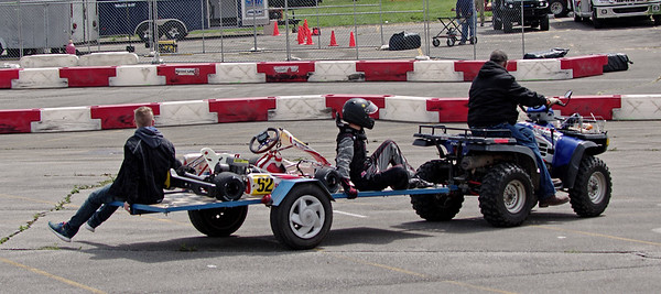 A driver and his disabled kart get a lift back to the pits to make repairs.