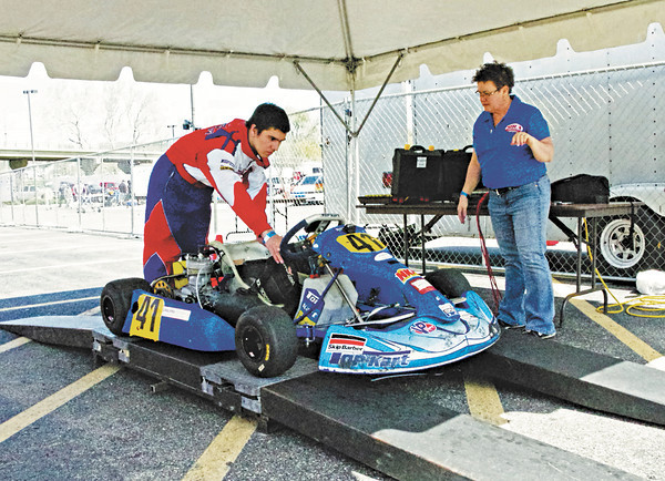 Cameron Smock of Plainfield, Indiana positions his kart on the scales for tech inspector Cindy Yeich prior to racing in the Mayor's Cup Grand Prix on Sunday.