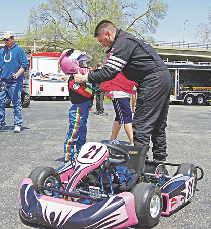Kart racer Jay McFall of Anderson assists his 6-year old daughter Kylan with her helmet as she prepares for her first ever kart race on Sunday at the Mayor's Cup Grand Prix.