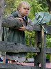 Reenactor Evie Grim ,3, stands on a fence and watches the Grand Fantastical Parade around the plantation grounds during the Goschenhoppen Historians' 48th annual Folk Festival on Friday August 8,2014. Photo by Mark C Psoras