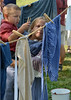 Reenactor Emma Williams holds her younger brother Zachary as they hang laundry in the 19th Century Homeskills area during the Goschenhoppen Historians' 48th annual Folk Festival on Friday August 8,2014. Photo by Mark C Psoras