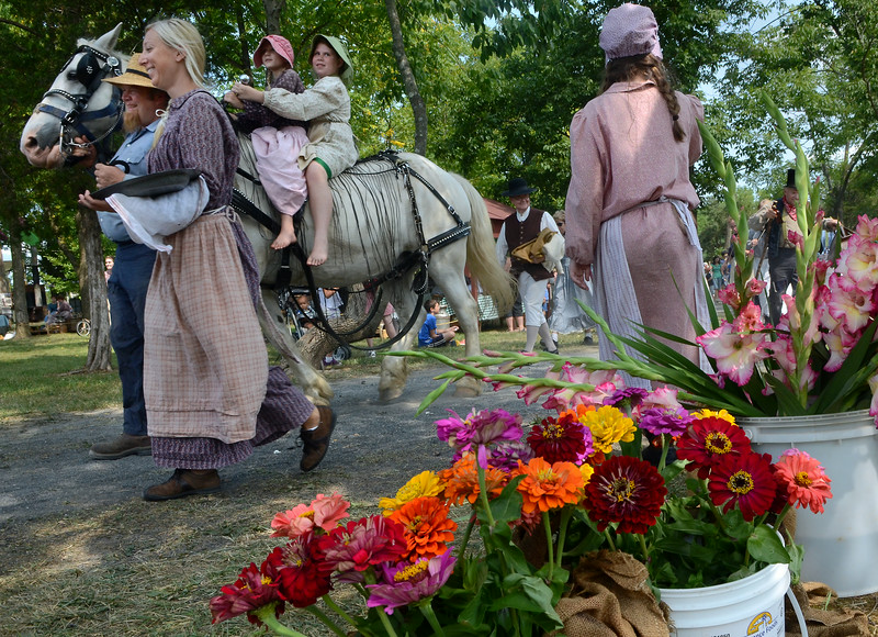 Sprays of flowers for sale are seen as reenactors take part in the Grand Fantastical Parade around the plantation grounds during the Goschenhoppen Historians' 48th annual Folk Festival on Friday August 8,2014. Photo by Mark C Psoras