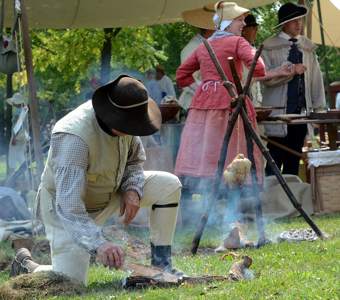 Revolutionary War reenactors with the 1st Continental Regimen Wayne Brunt flips fire cakes during the Goschenhoppen Historians' 48th annual Folk Festival on Friday August 8,2014. Photo by Mark C Psoras