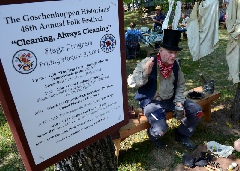 A festival itinerary sign is seen as 19th Century reenactors tell their stories during the Goschenhoppen Historians' 48th annual Folk Festival on Friday August 8,2014. Photo by Mark C Psoras