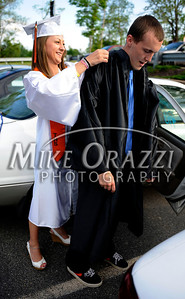 6/15/2011 Mike Orazzi | Staff Terryville High School Senior Grisilda Dinkollari helps C.J. Smith with his gown at THS graduation ceremony on Wednesday night.