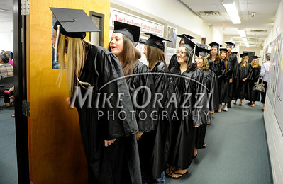 5/25/2011 Mike Orazzi | Staff Terrin Carrara peeks around the door at the start of the graduation ceremony at the Bristol Adult Education Center on Redstone Avenue in Bristol on Wednesday night.
