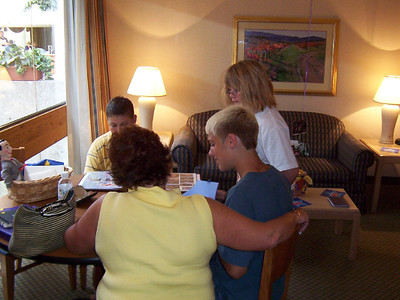 Fran, Brady, Cassie and Travis Bisenius looking at photographs at the graduation party