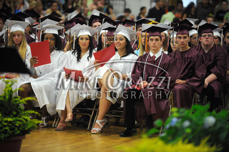 6/25/2013 Mike Orazzi | Staff<br /> Bristol Central High School graduates fan themselves to stay cool at Bristol Central on Tuesday night in Bristol.