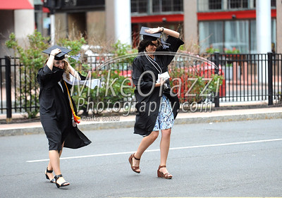 5/20/2017 Mike Orazzi | Staff Olivia McDonald and Katherine Diehl hold their caps as the run across a windy Trumbull Street toward the XL Center in Hartford for CCSU's graduation Saturday morning.