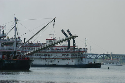 The Belle of Cincinnati, judge for the steamboat race, passes behind the Delta Queen