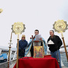 Record-Eagle/Keith King<br /> Lou Condos, from left, of Traverse City, Father Ciprian Streza of the Archangel Gabriel Greek Orthodox Church in Traverse City and Steve Bemis, of Kewadin, stand on the Clinch Park Marina pier as attendees look on Saturday, January 7, 2012 during the Great Blessing of the Waters.