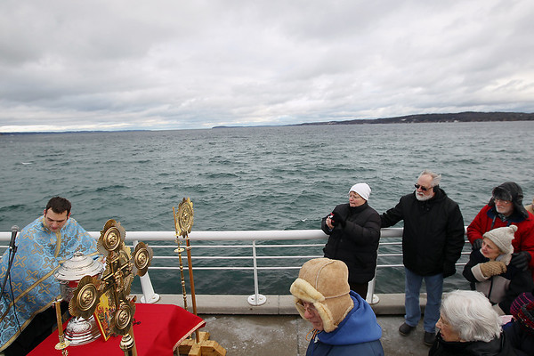 Record-Eagle/Keith King<br /> Father Ciprian Streza, left, of the Archangel Gabriel Greek Orthodox Church in Traverse City presides Saturday, January 7, 2012 as attendees stand near on the Clinch Park Marina pier during the Great Blessing of the Waters.