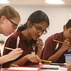 Greater Lowell Regional Knowledge Bowl finals at Tyngsborough High School. Chelmsford team members, from left, Hannah Wolman, Divya Sambasivan, and Nithin Chandra, work on the Math Round problems in the cafeteria. (SUN/Julia Malakie)