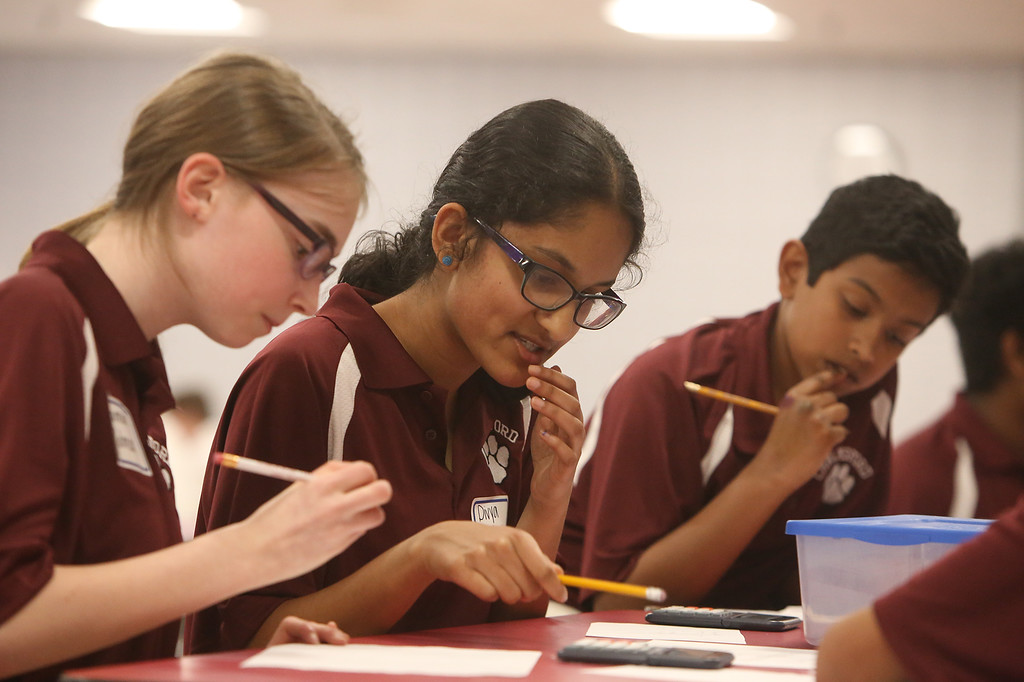 . Greater Lowell Regional Knowledge Bowl finals at Tyngsborough High School. Chelmsford team members, from left, Hannah Wolman, Divya Sambasivan, and Nithin Chandra, work on the Math Round problems in the cafeteria. (SUN/Julia Malakie)