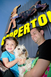 1/30/10—Under the historic Coppertone sign George Zamora, holds Blitz as Gianna Zamora, 2, give him a hug during the Environmental Green Dog party in Miami.