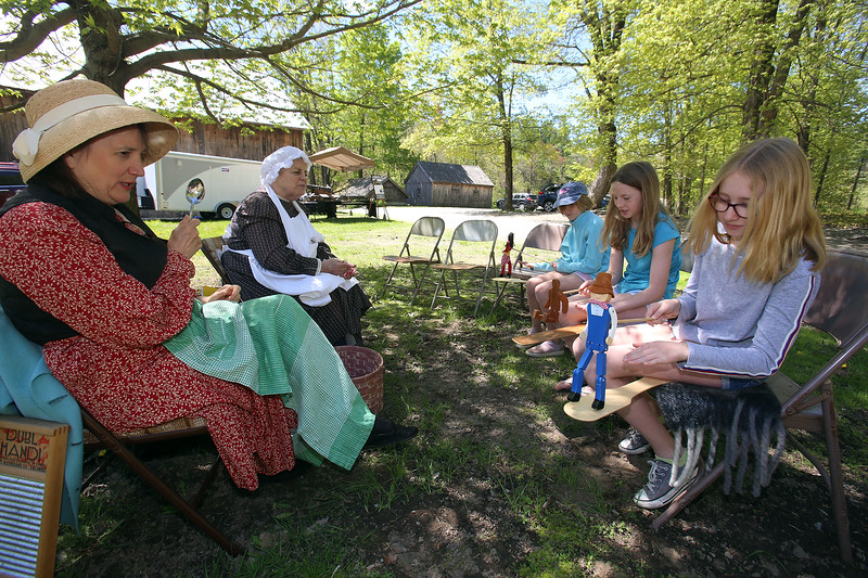 """Groton Womens Club holds Back in Time event at the Williams Barn, to show life in the 1700s in the community. From left, June Cloutier, Bonnie Marchesani, Mary Kubick, 10, Lily Burgess, 12, and Mary's sister Ellie Kubick, 12, sing and make music with colonial type instruments including """"dancing dolls"""" and spoons. (SUN/Julia Malakie)"""