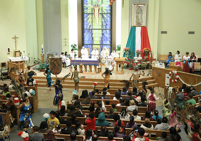 Approximately 40 St. Oliver Plunkett Church Hispanic dancers fill the aisles around the church performing their concheros style of dance before the congregation, the altar servers and the clergy.