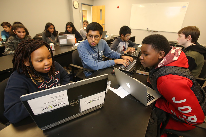 NETSCOUT and Shooting Stars Foundation host Star-Hacks on for middle and high school students. Hazel Mutindwa, 12, left, and her brother Kevin Mutindwa, 13, of Leominster, Shoumik Kundu, 15, of Chelmford, center, and Vishant Raajkumar, 14, of Chelmsford, left rear, and Ben Blute, 15, right rear, both of Chelmsford, work on FoodMatch, a game to raise awareness about food waste. (SUN Julia Malakie)
