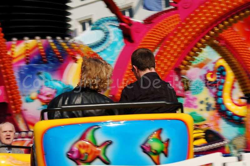 Image of a couple on the Polyp, kind of an Octopus with seats turning around and going up and down on music (from a soft Waltz to more popular up-beat music). It took me some hundreds of photos to get at least one keeper (the cars go so speedy and also move up and down so that you can't focus accurately and fast enough). The Polyp was a new attraction at the Halfvastenfoor (Mid Lent Fun Fair) in Ghent (Gent), Belgium. Shot with the Nikkor 18-200mm zoom lens. No post processing at all.