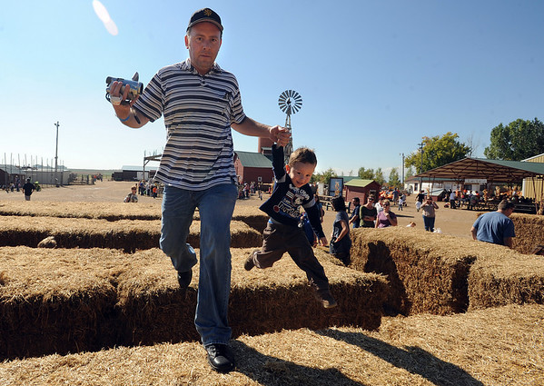 """Peter Lendel and his son, Merrick, 3, race around the hay bails at Anderson Farms on Thursday.<br /> For more photos and a video of Anderson Farm, go to  <a href=""""http://www.dailycamera.com"""">http://www.dailycamera.com</a>.<br /> Cliff Grassmick / October 7, 2010"""