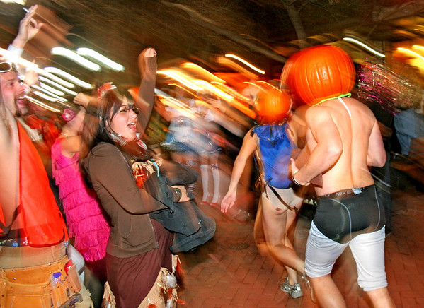 Amanda Serett cheers on two pumpkin runners as they run through the crowd on the Pearl Street Mall on Halloween.<br /> Photo by Will Morgan/ For The Camera