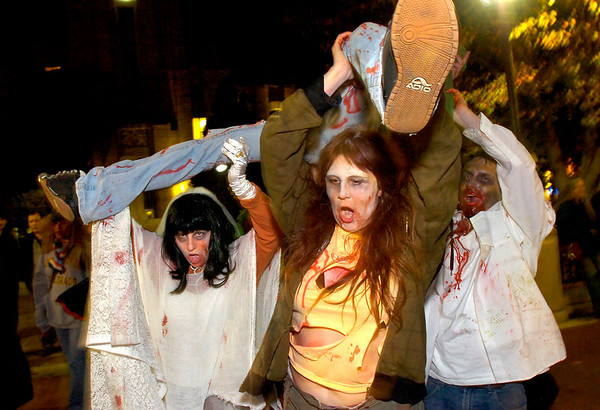 "Marsha Steckling, at left and fellow zombie Jeanne Steckling grab a ""victim"" as part of their Zombie Mall Crawl on the Pearl Street Mall Halloween evening.<br /> Photo by Paul Aiken"