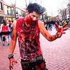 Adrian Ruiz, of Denver, uses the zombie walk to chase down pedestrians on the Pearl Street Mall Halloween evening.<br /> Photo by Paul Aiken