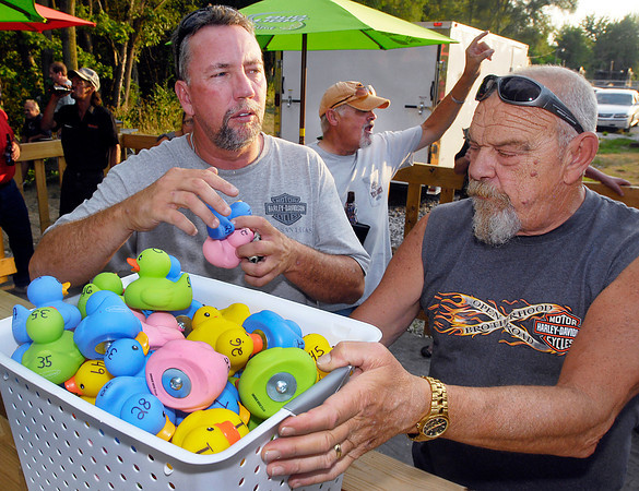 Bill Gilbert and Mike Farley load up the ducks as Nick Hinton, background, shouts out to the patrons that its post time for the race.
