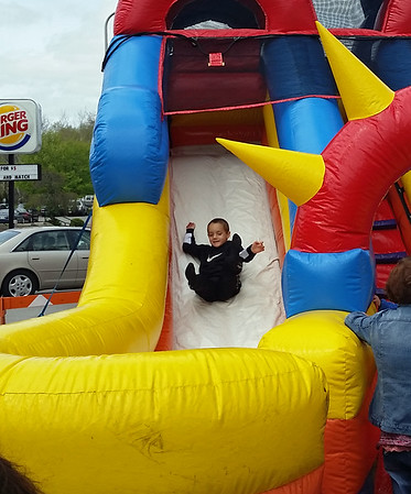 A youngster enjoys an inflatable slide set up on West Washington Street during Y Healthy Kids Day.