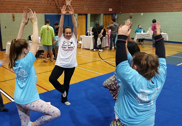 Allisyn Wolfe of Big Brothers Big Sisters leads a group of girls in some healthy stretching.
