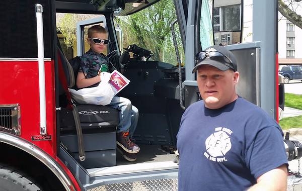 Chester Burrows, 8, or New Castle sits in a city firetruck while firefighter Matt Presnar waits outside.
