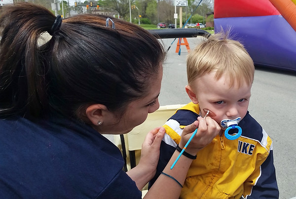 Gunner Peters, 2, of New Castle gets a football painted on his face by Keona Pagley at the Children's Advocacy table during Y Healthy Kids Day.