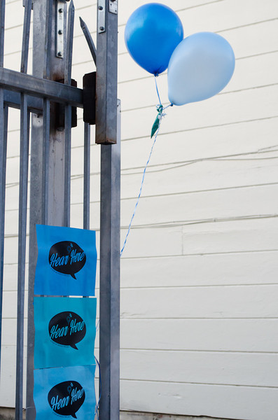 Balloons and Hear Here signs on gate. KALW Mission Arts and Performance Project (MAPP) June 2012, The Polish Club, 3040-22nd St. at Shotwell St., Mission district, San Francisco, California.