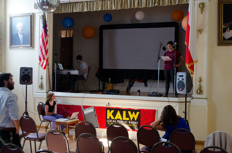 Molly Samuel rehearsing on stage; Wendy Baker, computer. KALW Mission Arts and Performance Project (MAPP) June 2012, The Polish Club, 3040-22nd St. at Shotwell St., Mission district, San Francisco, California.