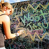 Dannielle Miller, 18, of Fort Lupton, works on a chalk drawing she created on a giant graffiti wall during the Heaven Festival on Saturday, July 31, at the Union Reservoir in Longmont. <br /> Jeremy Papasso/ Camera