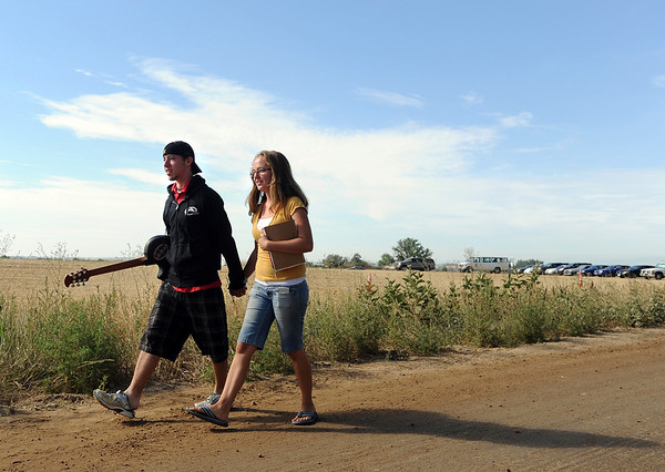"Jesse Shahan, left, and  Andrea Weron, both of Laramie, head back to their car after helping out at the Heaven Fest site.<br /> Staff and volunteers spent Sunday taking down stages and tents, and generally cleaning up the site of Heaven Fest, the one-day Christian music festival held at Union Reservoir near Longmont.<br /> For more photos  of the clean up, go to  <a href=""http://www.dailycamera.com"">http://www.dailycamera.com</a><br />  Cliff Grassmick / August 1, 2010"