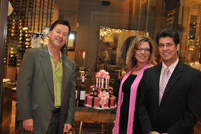 "Photograph of Double Helix owner Raymond Nisis with Event Planner Kaleta and PR Harvey Blanc. Hello Kitty, she is a Japanese cartoon cat invented by the design company Sanrio in 1974. She was created without a mouth because she speaks from the heart so no one language is necessary. From the famous Lombardi region in Italy, Hello Kitty offers 4 distinct DOC certified (Vino a Demoninazione di Origine Controllata) wines. That means these wines are grown in a specific region with very specific rules of production they must follow. Try the  Hello Kitty Angel White made from Pinot Noir free run juice or the  Hello Kitty Devil Red that's garnet red in color with a wild flowers bouquet. You might also like the Hello Kitty Sparkling Brut Rose with its deep red pink hue and rose petal nose or the semi-sweet sparkler with delicate bubbles known as the Hello Kitty Sparkling ""Sweet Pink."" Photograph by Las Vegas photographer Mark Bowers."